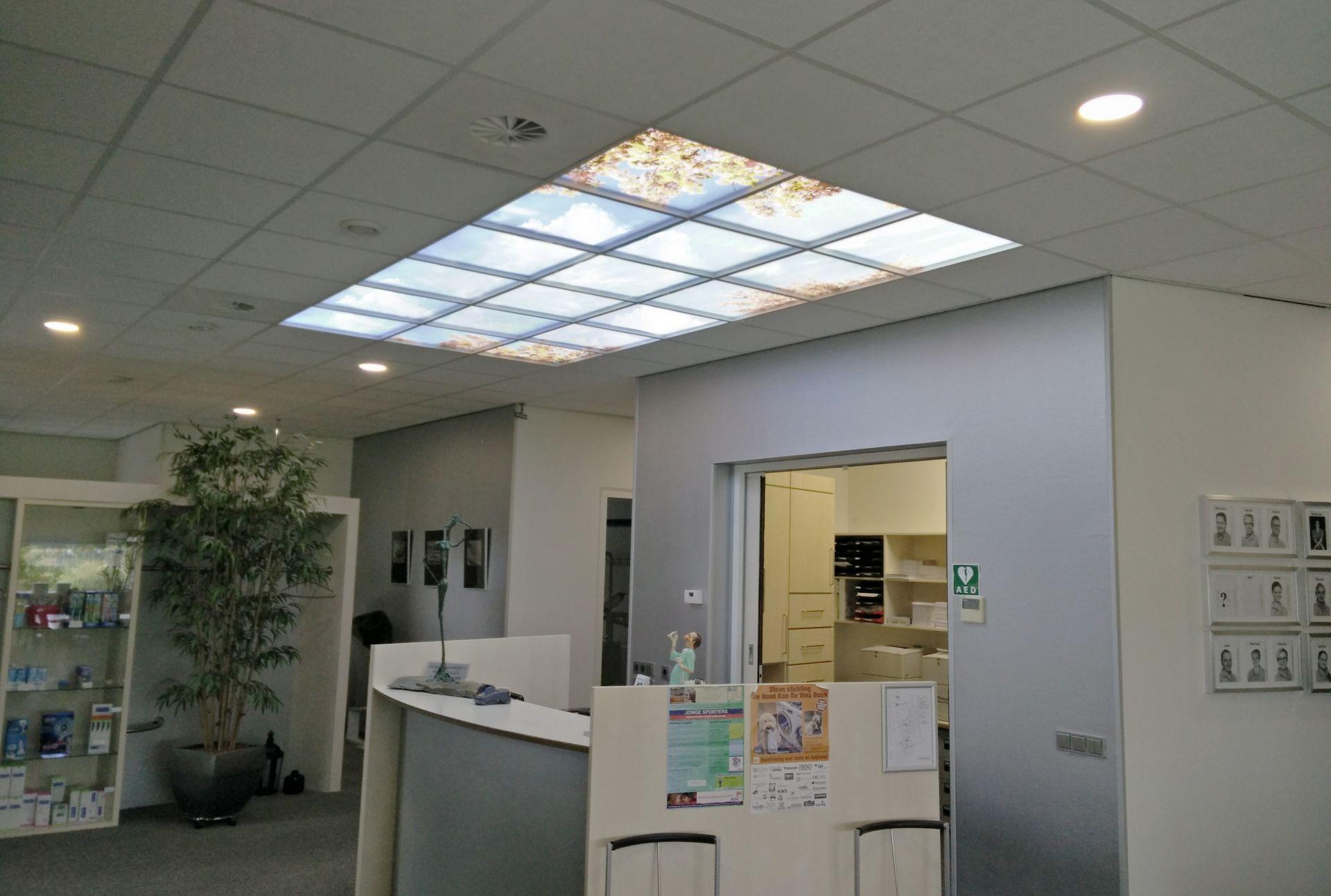 Balie bij de tandarts met een wolkenplafond. De foto print van het wolkenplafond word verlicht met meerdere LED panelen van 60x60 cm