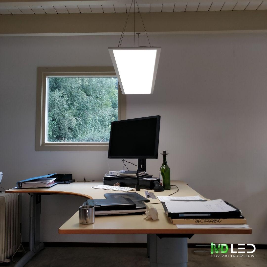 Werkplek verlicht met LED paneel. Het LED paneel is gependeld boven het bureau opgehangen.