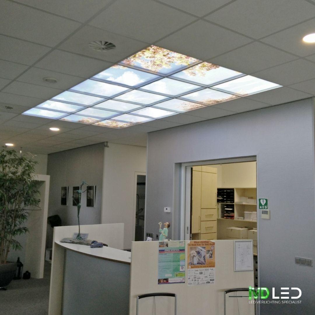 Balie bij de tandarts met een wolkenplafond. De foto print van het wolkenplafond word verlicht met meerdere LED panelen van 60x60